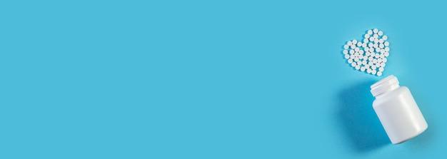 Weiße pillen in herzform mit flasche auf blauem hintergrund. machen sie sich für werbung oder andere ideen lustig. medizin- und gesundheitskonzept. medizinisches breites banner mit platz für text. Premium Fotos