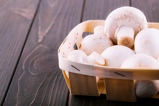 Weiße pilze liegen auf korb auf dunklem holztisch Kostenlose Fotos