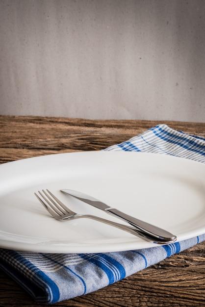 Weiße platte auf einer serviette und silber gabel, messer. auf hölzerner tischplatte Premium Fotos