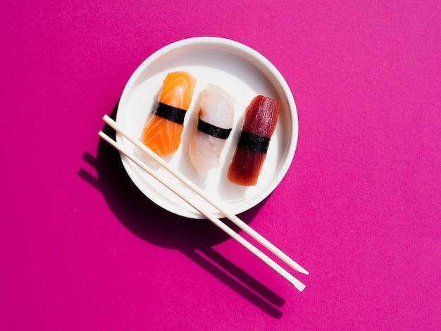 Weiße platte von sushi mit hiebstöcken auf einem rosenhintergrund Kostenlose Fotos