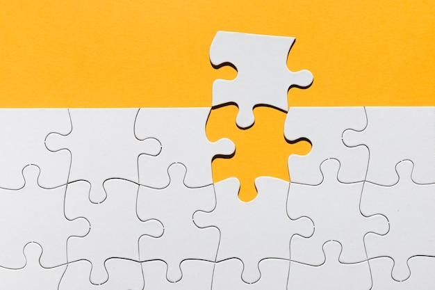 Weiße puzzlebeschaffenheit auf gelbem hintergrund Kostenlose Fotos