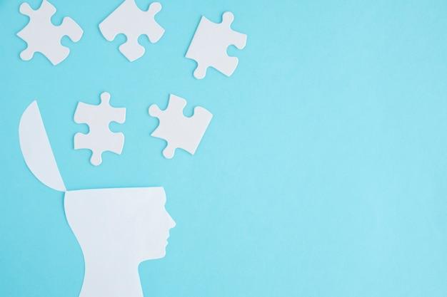 Weiße puzzlespiele über dem offenen kopf auf blauem hintergrund Kostenlose Fotos