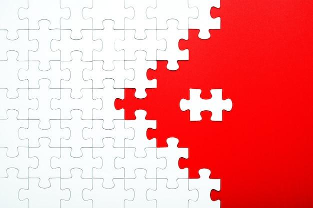 Weiße puzzleteile auf einem roten hintergrund getrennt Premium Fotos