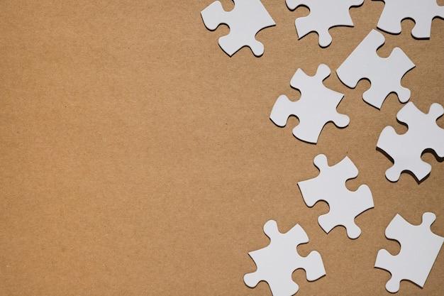 Weiße puzzleteile auf hintergrund des braunen papiers Kostenlose Fotos
