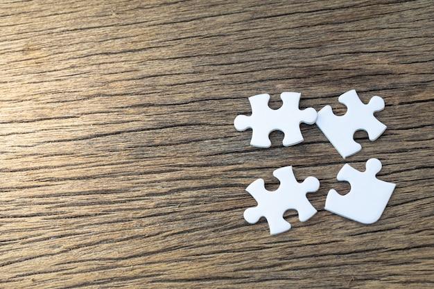 Weiße puzzleteile liegen auf einem holztisch Premium Fotos
