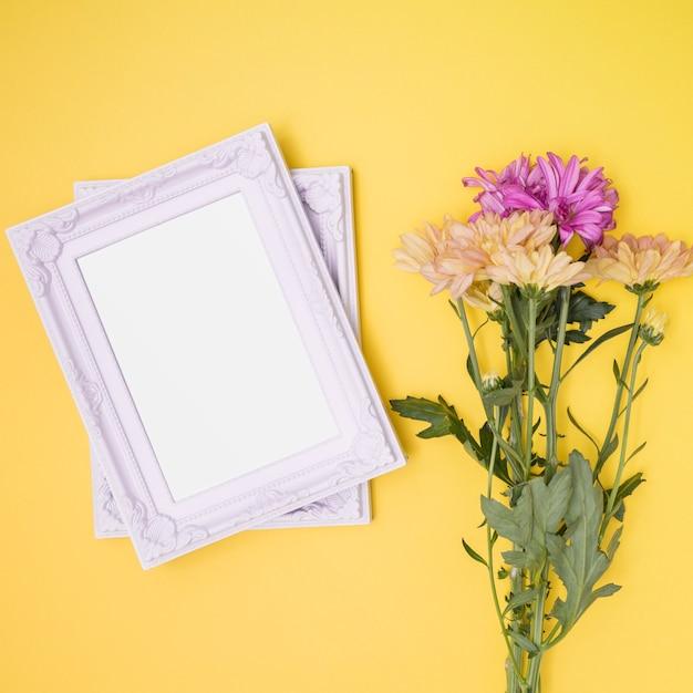 Weiße rahmen neben blumenstrauß Kostenlose Fotos