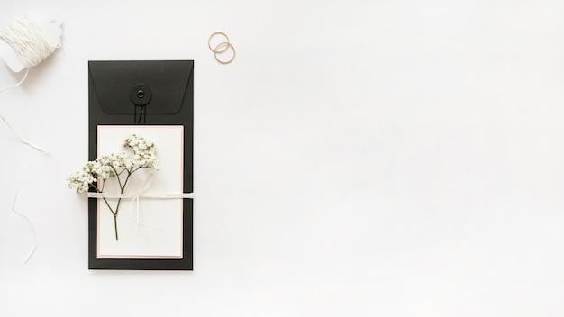Weiße saiten; eheringe und grußkarte mit baby-atem blumen auf weißem hintergrund Kostenlose Fotos