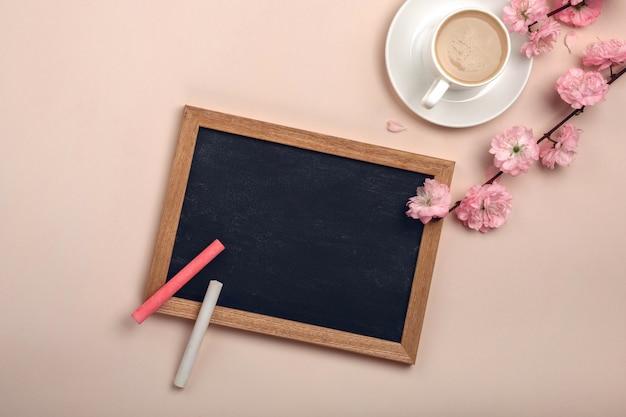 Weiße schale mit cappuccino, kirschblüte blüht, kreidebrett auf einem pastellrosahintergrund. Premium Fotos