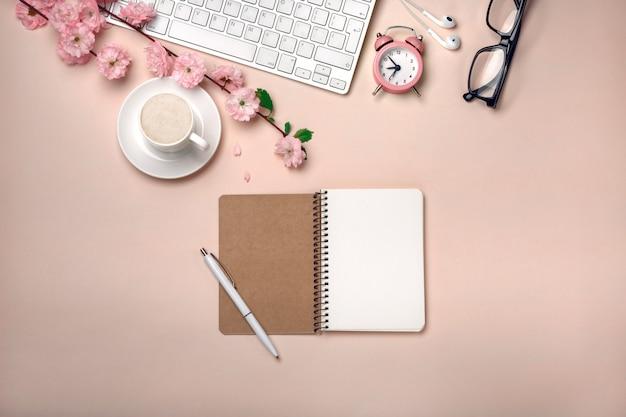 Weiße schale mit cappuccino, kirschblüte blüht, tastatur, wecker, notizbuch auf einem pastellrosahintergrund. Premium Fotos