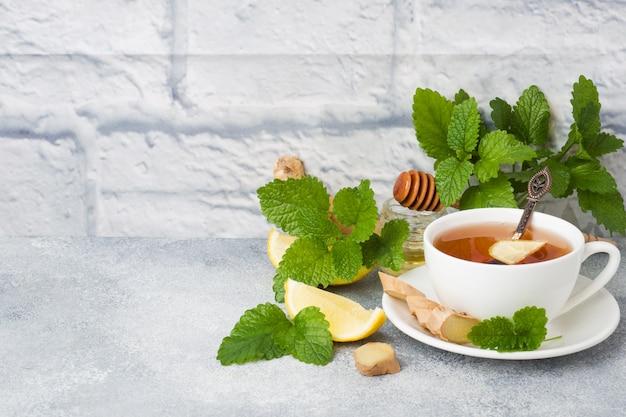 Weiße schale mit natürlicher kräuterteeingwer-zitronenminze und -honig. Premium Fotos