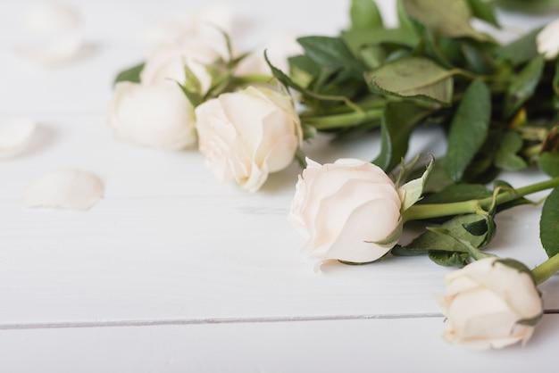 Weiße schöne rosen auf hölzernem schreibtisch Kostenlose Fotos