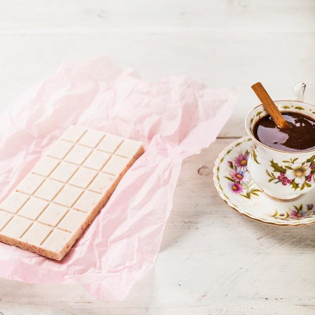 Weiße schokolade in papier mit heißer schokolade in der tasse eingewickelt Kostenlose Fotos