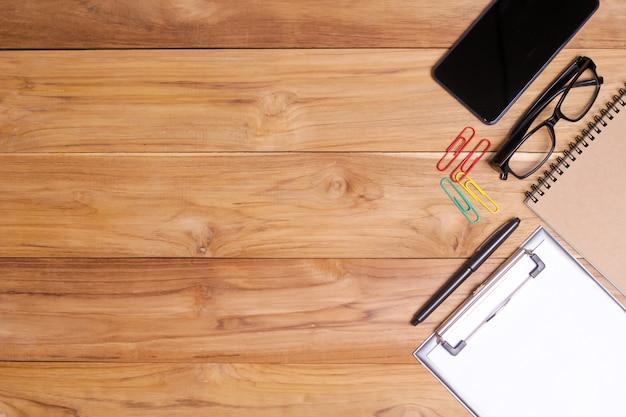 Weiße schreibtischtabelle mit brillennotizbuch, büroanlage, stift, klipps und smartphone. Premium Fotos
