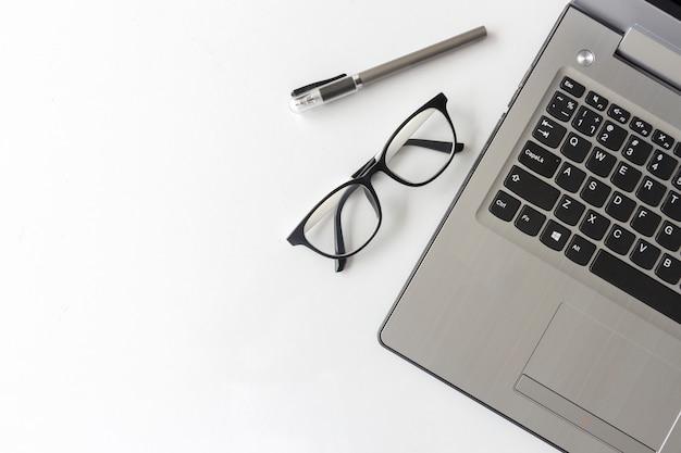 Weiße schreibtischtabelle mit bürobedarfsnotebook und -brillen Premium Fotos