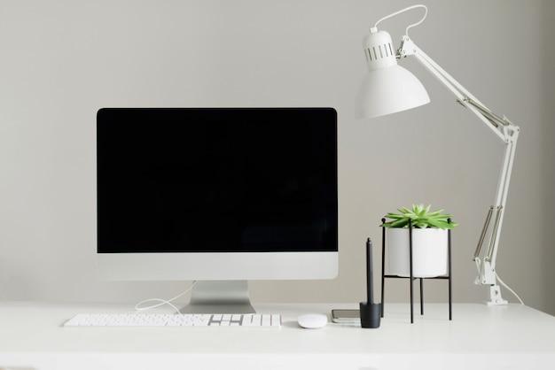 Weiße schreibtischtabelle mit computertastatur, maus, monitor, grafischer tablette, smartphone, saftiger anlage und anderem büroartikel. Premium Fotos