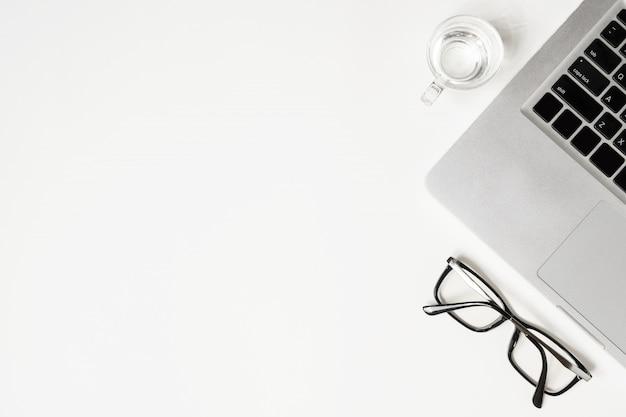Weiße schreibtischtabelle mit laptop, glas trinkwasser und brillen. Premium Fotos