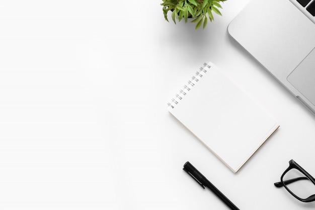Weiße schreibtischtabelle mit leerem notizbuch, laptop und anderem büroartikel. draufsicht mit kopienraum, flache lage. Premium Fotos