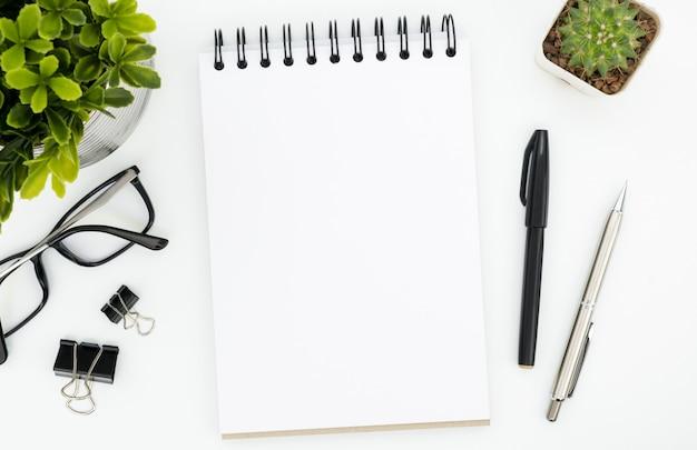 Weiße schreibtischtabelle mit leerer notizbuchseite und -versorgungen. draufsicht, flach zu legen. Premium Fotos