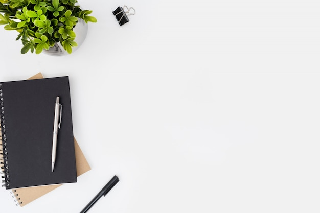 Weiße schreibtischtabelle mit notizbüchern und stiften. Premium Fotos