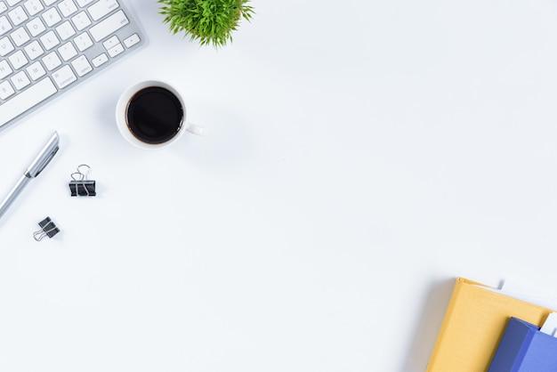 Weiße schreibtischtabelle und -ausrüstung für das arbeiten mit schwarzem kaffee in der draufsicht und im flachen strahlnkonzept. Premium Fotos