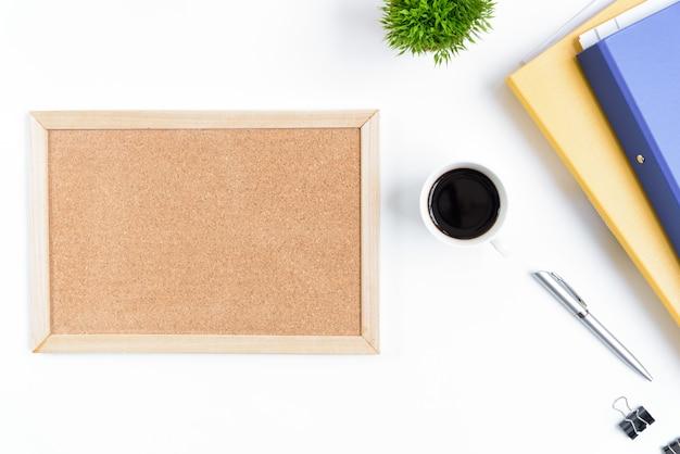Weiße schreibtischtabelle und -ausrüstung für das arbeiten mit schwarzem kaffee und leerem brett in der draufsicht und im flachen strahlenkonzept. Premium Fotos