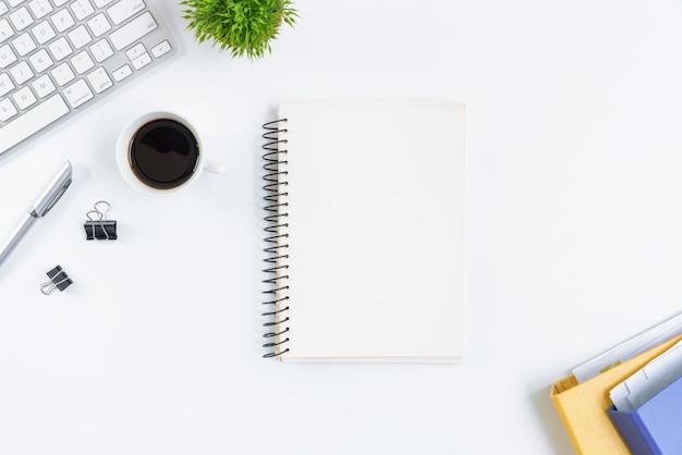 Weiße schreibtischtabelle und -ausrüstung für das arbeiten mit schwarzem kaffee und weißbuch in der draufsicht und im konzept des flachen strahls. Premium Fotos