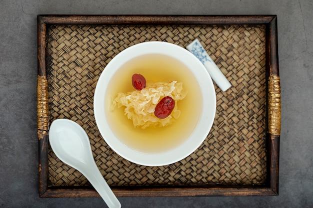 Weiße schüssel mit suppe auf einem hölzernen brett Kostenlose Fotos
