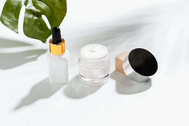 Weiße serumflasche und cremetiegel, modell der schönheitsproduktmarke. draufsicht auf den weißen hintergrund. Premium Fotos