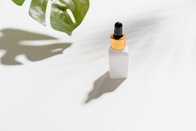 Weiße serumflaschencreme, modell der schönheitsproduktmarke in der flachen lage Premium Fotos