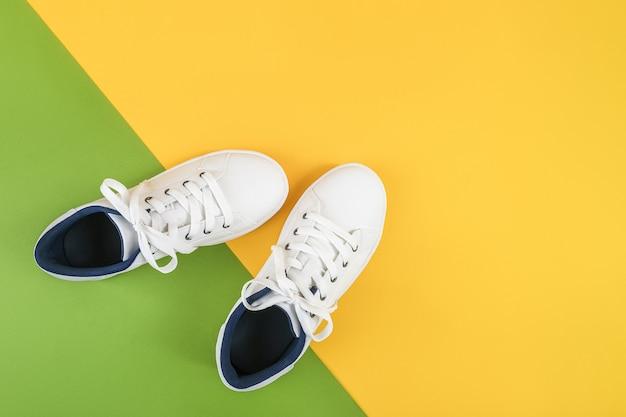 Weiße sportschuhe, turnschuhe mit schnürsenkeln auf grünem und gelbem hintergrund. sport-lifestyle-konzept Premium Fotos