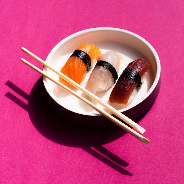 Weiße sushischüssel mit essstäbchen auf rosafarbenem hintergrund Kostenlose Fotos