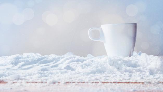 Weiße tasse auf schnee gelegt Kostenlose Fotos
