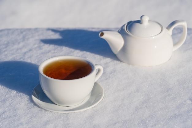 Weiße tasse heißen tees und teekanne auf einem bett aus schnee und weißem hintergrund, schließen sie oben. konzept des weihnachtswintermorgens Premium Fotos