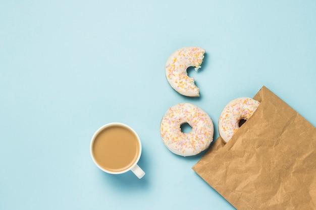 Weiße tasse mit kaffee oder tee und papiertüte mit frischen köstlichen süßen donuts auf einem blauen hintergrund. konzept von fast food, bäckerei, frühstück, süßigkeiten. minimalismus. flache lage, draufsicht. Premium Fotos