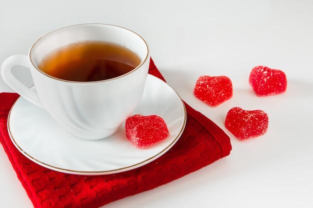 Weiße tasse mit tee auf einer roten serviette und herzförmiger marmelade auf einem weißen hintergrund. symbol der liebe, valentinstag, geschenkkarte Premium Fotos