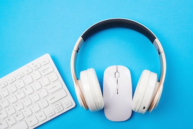 Weiße tastatur, maus und kopfhörer auf blauem hintergrund, draufsicht. speicherplatz kopieren. fernunterricht und arbeit. Premium Fotos