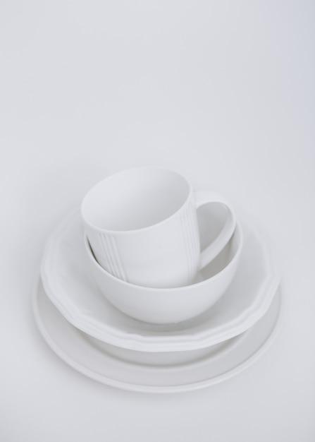 Weiße teller drei teller und eine tasse auf einem weißen hintergrund Kostenlose Fotos