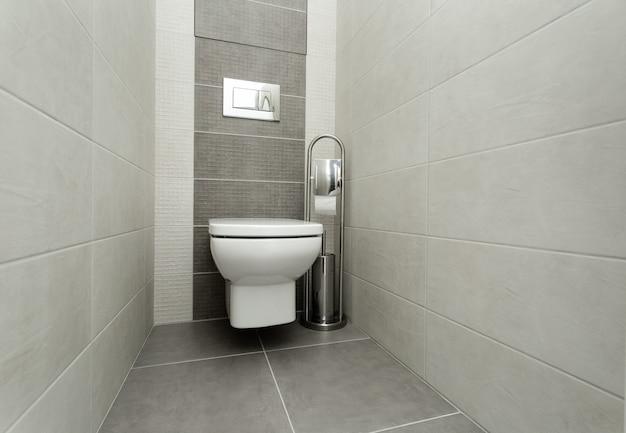 Weiße toilettenschüssel im modernen badezimmer mit papierhalter und toilettenbürste. Premium Fotos