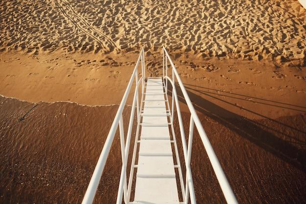 Weiße treppe führt zum strand vom boot Kostenlose Fotos