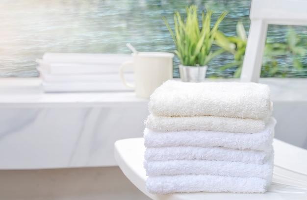 Weiße tücher auf weißem strandstuhl mit kopienraum auf unscharfem blauem seehintergrund Premium Fotos