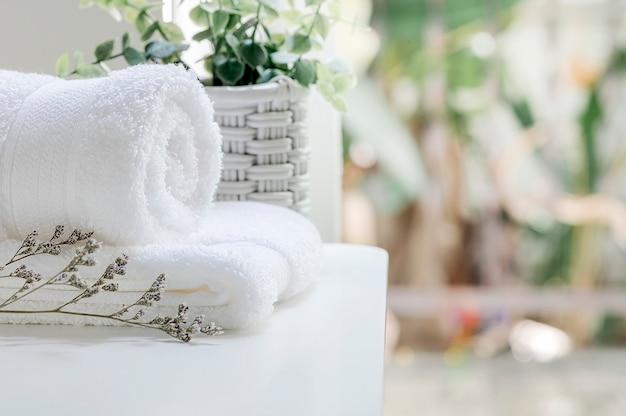 Weiße tücher und houseplant der nahaufnahme auf weißer tabelle nahe dem fenster im modernen haus, kopienraum. Premium Fotos