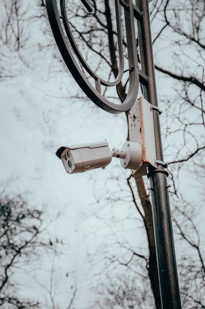 Weiße überwachungskamera, die an einer stange hängt. die kamera beobachtet die bestellung auf den straßen und in den parks. kamera auf einem pfosten in einem park. seitenansicht und gerade Premium Fotos