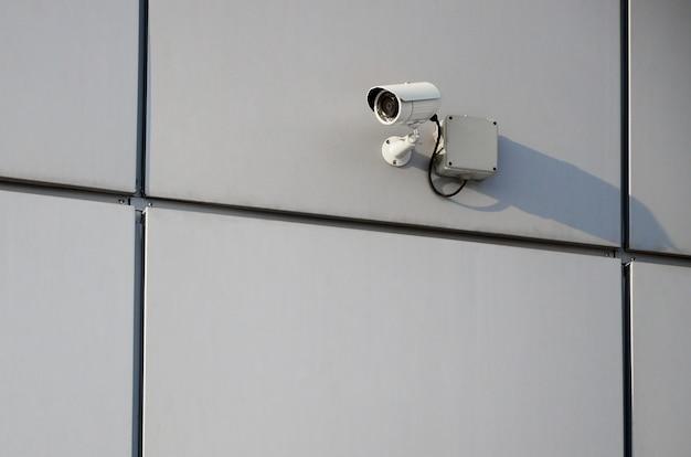 Weiße überwachungskamera in die metallwand des bürogebäudes eingebaut Premium Fotos