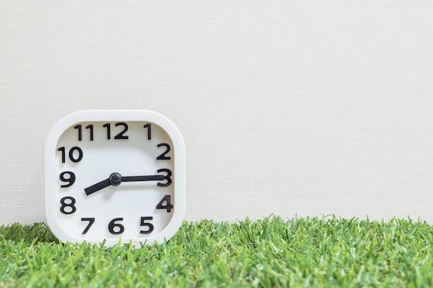 Weiße uhr der nahaufnahme für verzieren show viertel nach acht oder 8:15 morgens auf grünem kunstrasenboden Premium Fotos
