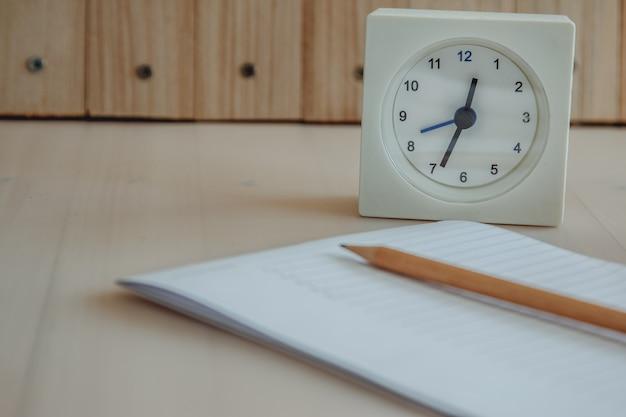 Weiße uhr in der nähe von notebook und bleistift Premium Fotos
