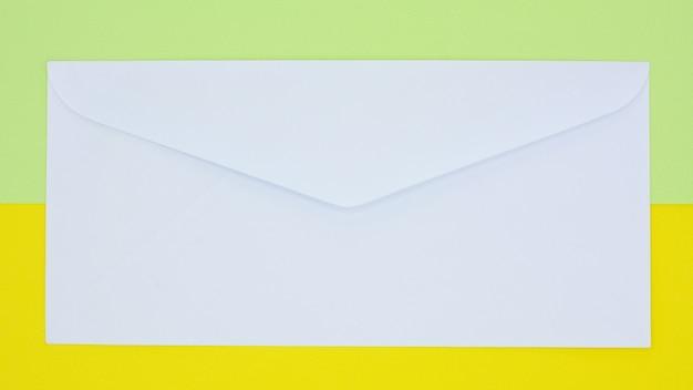 Weiße umschlagpost auf gelbem und grünem hintergrund Premium Fotos
