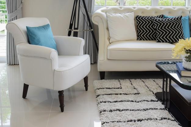 Weiße und blaue kissen auf einer weißen ledercouch im weinlesewohnzimmer Premium Fotos