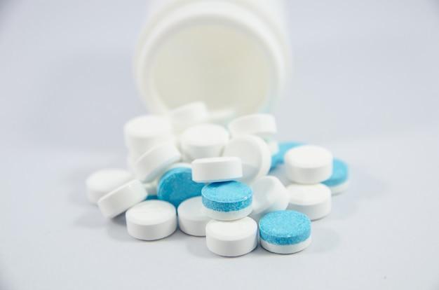 Weiße und blaue pille auf weißem blackground mit flasche Premium Fotos