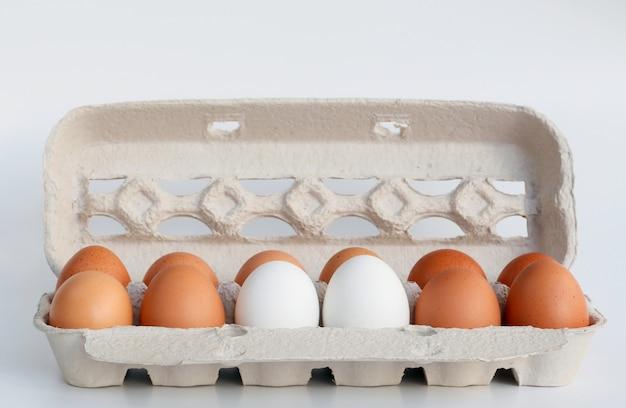 Weiße und braune eier im karton Premium Fotos
