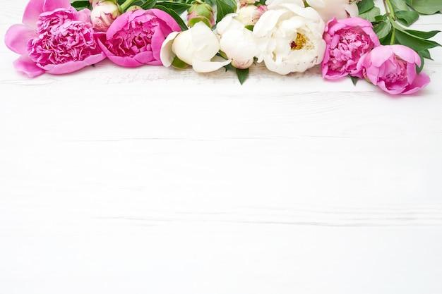 Weiße und rosa pfingstrosen auf weißem holztisch. Premium Fotos